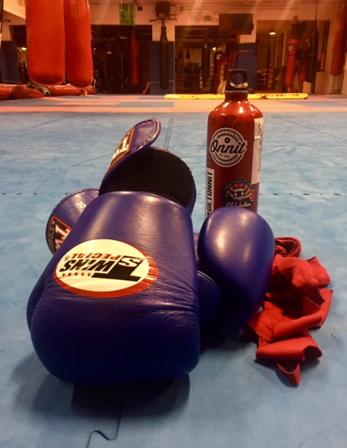 Boxing gloves in a gym with hand wraps and a water bottle